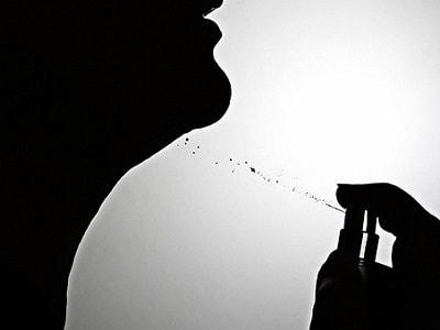 香水を吹きかける女性の影