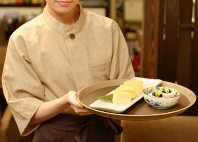 飲食店でアルバイトをする女子大生